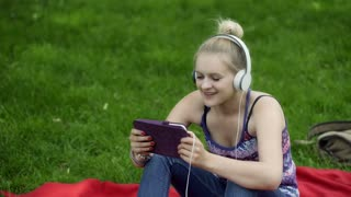 Girl listening music on tablet and smiling to the camera