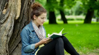 Girl looking for something in the book while sitting in the park