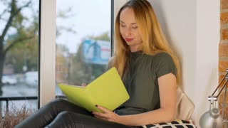 Girl looking happy while writing thoughts in her diary by the window