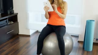 Girl looking on tablet and exercising arms while sitting on the ball, steadycam