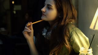 Girl looking thoughtful and writing her thoughts in journal, steadycam shot