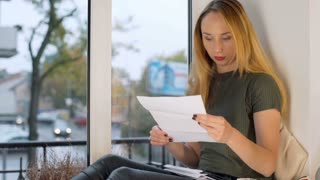 Girl looks irritated while checking her bills and drinking wine