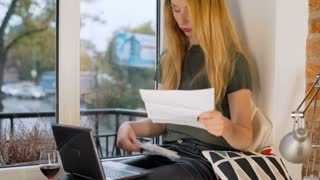 Girl looks surprised while checking her bills, steadycam shot