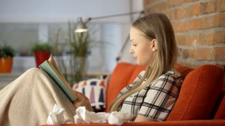 Girl looks very ill while sitting under blanket on the sofa and reading book