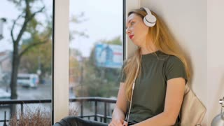 Girl looks very sad while listening music on headphones by the window