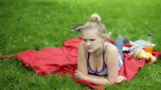 Girl lying alone on the blanket in the park and worrying