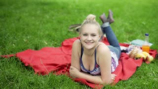 Girl lying on the blanket in the park and smiling to the camera