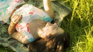 Girl lying on the meadow and playing with flowers
