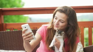 Girl playing with kitty and trying to do selfie with him