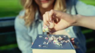 Girl playing with petals on the book and blowing them