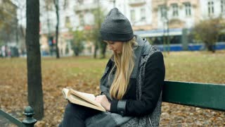 Girl reading book in the park and smiling to the camera, steadycam shot