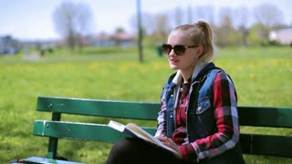Girl reading book on the bench and smiling to the camera