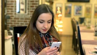 Girl reading message on smartphone and receives good news, steadycam shot
