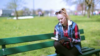 Girl relaxing on the bench and reading book