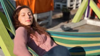 Girl relaxing while having a nap on hammock and catching sun