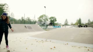 Girl riding on rollerblades in skate park and smiling to the camera