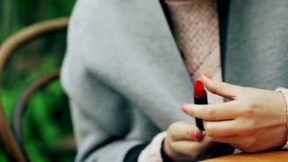 Girl sitting and playing with red lipstick in hands