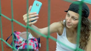 Girl sitting behind net and doing selfies on smartphone, steadycam shot