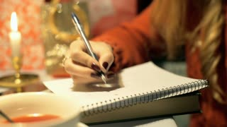 Girl sitting by the table and writes something in her notebook