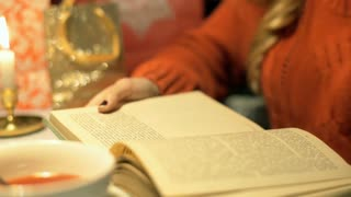 Girl sitting by the table at christmas evening and reading book