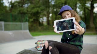 Girl sitting in skate park and doing selfies on tablet