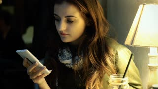 Girl sitting in the cafe and browsing internet on smartphone, steadycam shot