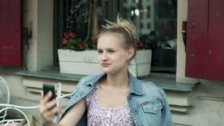 Girl sitting in the cafe and doing selfie on smartphone