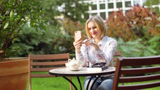Girl sitting in the outdoor cafe and doing selfies on smartphone