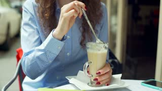 Girl sitting in the outdoor cafe and eating cream from a latte