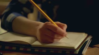 Girl sitting in the restaurant and writing something in her journal