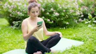Girl sitting on exercising mat in the park and reading sms on smartphone