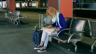 Girl sitting on platform and searching something on the map