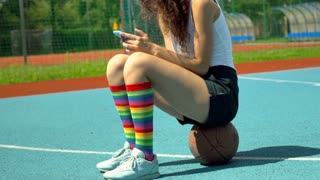 Girl sitting on the ball and browsing internet on smartphone, steadycam shot