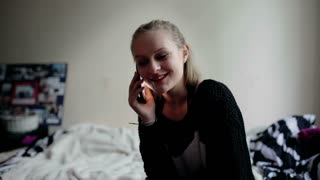 Girl sitting on the bed and chatting on cellphone