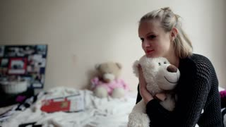 Girl sitting on the bed and cuddling a teddy bear