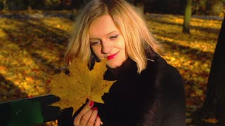 Girl sitting on the bench and holding maple leaf, slow motion shot