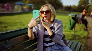 Girl sitting on the bench and improving her makeup while looking on smartphone