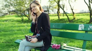 Girl sitting on the bench in park and talking on cellphone