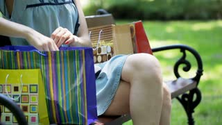 Girl sitting on the bench in the park and checking her news purchase