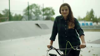 Girl sitting on the bike in skate park and smiling to the camera
