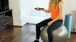 Girl sitting on the exercising ball and watching television, steadycam shot