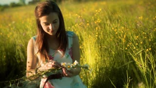 Girl sitting on the meadow and doing grommet from daisies
