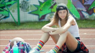 Girl sitting on the sports field in colorful socks and doing serious look to the