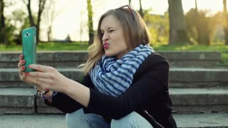 Girl sitting on the stairs and doing selfies on smartphone