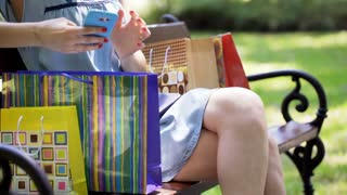 Girl sitting with her shopping bags on the bench and texting on smartphone