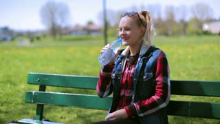 Girl smiling to the camera and drinking water on the bench