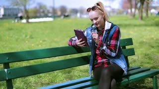 Girl smiling to the camera and using tablet in the park