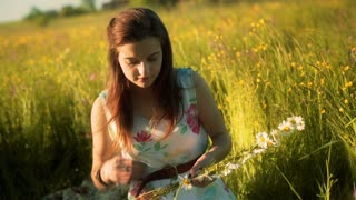 Girl smiling to the camera on the meadow and doing grommet