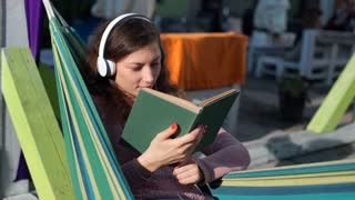 Girl smiling to the camera while listening music and reading book on hammock