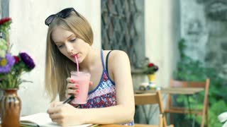 Girl smiling to the camera while writing in journal and drinking cocktail